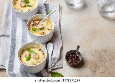 Chicken julienne and mushrooms in portion forms on a light background