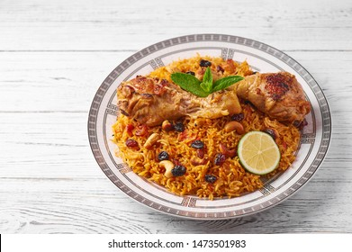 Chicken Kabsa known as Biryani or Danbauk at white wooden background. Kabsa is saudi arabian cuisine dish. It cooks with basmati rice, chicken, spices, tomatoes, nuts, raisins. Copy space.