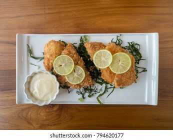 Chicken and kale fried with lemon and mayonnaise sauce on wood table at restaurant. top view.
