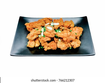Chicken Karaage, Japanese Fried Chicken with green onion slice on the Long black plate. Isolated on white