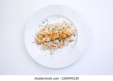chicken kebab with barley on the white plate