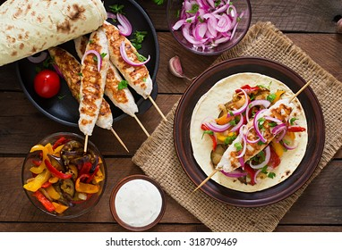 Chicken kebab with grilled vegetables and tortilla wrap. Top view