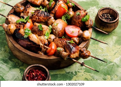 Chicken kebab on skewers with mushrooms and tomato.Bbq meat on wooden skewers