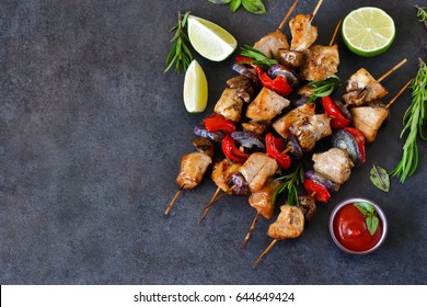 Chicken kebab on skewers with mushrooms and peppers and barbecue sauce on a black background. Food for a picnic.
