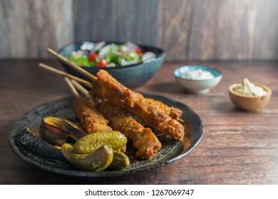 Chicken Kebab with Satay Sauce Salad Gherkins Hommus and Tzatziki
