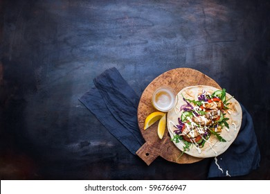 Chicken kebab with vegetables in pita bread and a glass of beer with lemon on a wooden tray on a metal counter. View from above. Dark metallic background.