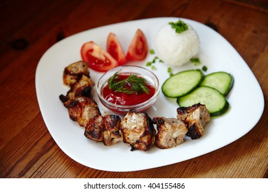 Chicken kebabs and cucumber salad on wooden background, top view. Kebabs - grilled meat and vegetables.