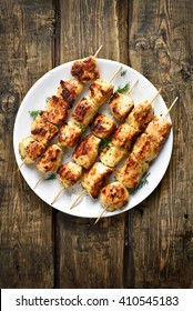 Chicken kebabs on wooden background, top view