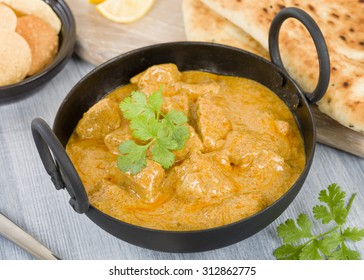 Chicken Korma - Chicken on a mildly spiced creamy sauce served with naan bread and poppadoms. Indian cuisine.