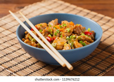 Chicken kung pao. Fried chicken pieces with peanuts and peppers. Front view.