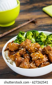 Chicken lacquered with a sweet soy teriyaki sauce in a white bowl. Garnished with rice and broccoli. Chopsticks, brown wooden table.
