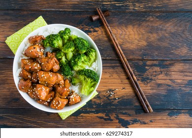 Chicken lacquered with a sweet soy teriyaki sauce in a white bowl. Garnished with rice and broccoli. Chopsticks, brown wooden table, top view.