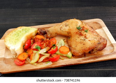 Chicken leg roasted with fried vegetables and garlic bread in wood board on black table