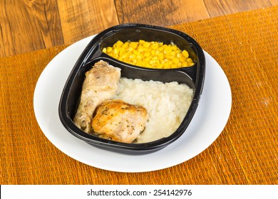 Chicken leg and thigh in plastic microwave dish with mashed potatoes and whole-grain corn.  Typical bland appearance of TV Dinner.