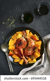 Chicken legs baked with pumpkin and orange on a black plate on a stone,concrete or slate background.Top view.