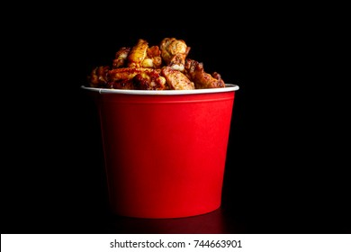 Chicken legs in a bucket. Red bucket is on a slate plate. Fried chicken. Close up.