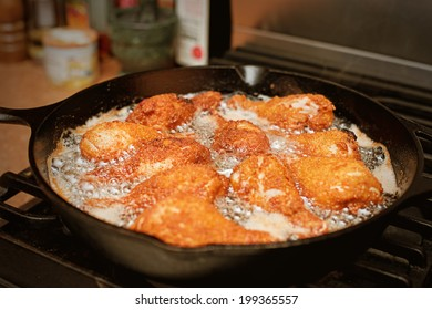 Chicken legs frying in a pan