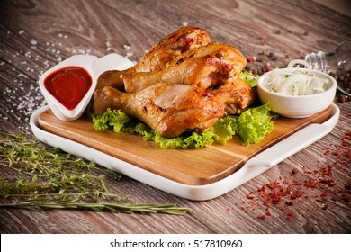Chicken legs grilled on a wooden board with white cup and around the seasoning spilling razmorin concept fasfud - Shutterstock ID 517810960