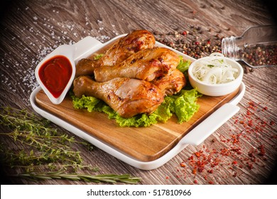 Chicken legs grilled on a wooden board with white cup and around the seasoning spilling razmorin concept fasfud