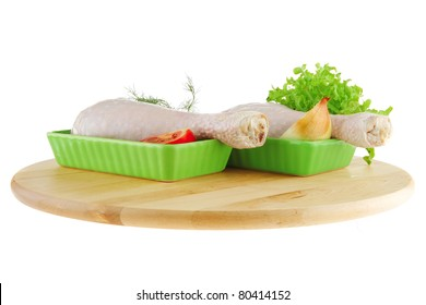 chicken legs on wooden plate over white