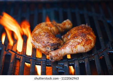 chicken legs spiced by special spice blend on bbq grill with flame