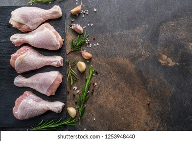 Chicken legs with spices and salt  ready for cooking on cutting board.