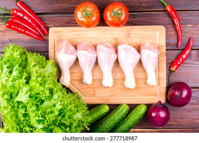 Chicken legs and vegetables on an old table: tomatoes, cucumbers, pepper, onions, lettuce leaves