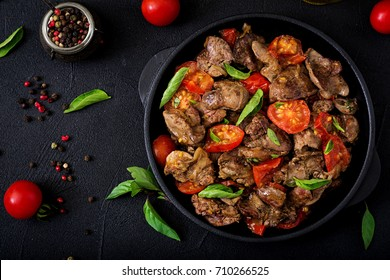 Chicken liver (offal) with onions and tomatoes in a frying pan in Armenian. Flat lay. Top view.
