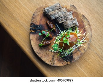 Chicken liver pate with fig jam and wholewheat brown bread decorated with pea greens (pea shoots)  on a wooden board. from above, diagonal