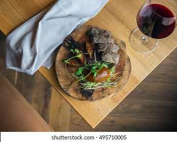 Chicken liver pate with fig jam and wholewheat brown bread decorated with pea greens (pea shoots)  on a wooden board. Red wine in a glass aside. from above, diagonal
