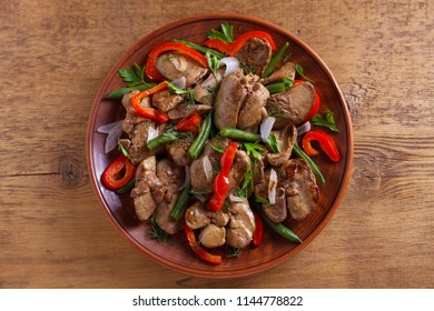 Chicken liver with vegetables: red paprika, green beans and onion. View from above, top studio shot