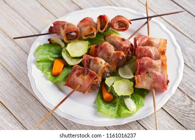 Chicken liver wrapped with bacon on skewers. Grilled liver kebabs with vegetables