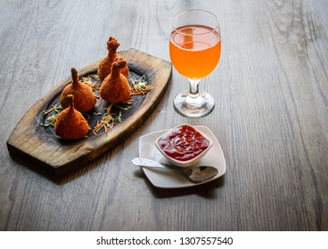 Chicken lollypops with a glass of fanta/mirinda with tomato sauce on a wooden table
