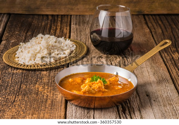 Chicken Madras served with a glass of red wine.