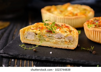 Chicken meat mini pie on the wooden board on table background, closeup with copy space, rustic style