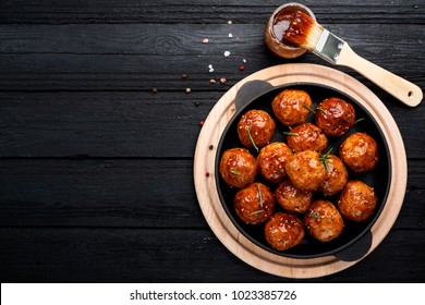 Chicken Meatballs with glaze on black wooden  background. top view.