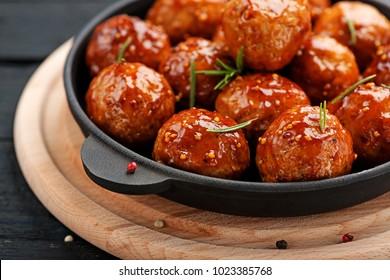 Chicken Meatballs with glaze on black wooden  background.