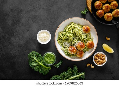 Chicken meatballs with spaghetti and green kale cashew pesto sauce. Top view.