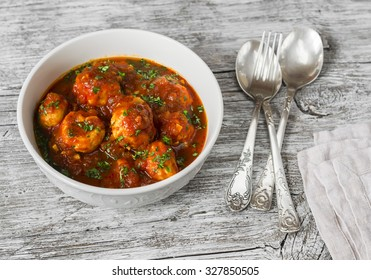 chicken meatballs with tomato sauce in a white bowl on bright wooden surface. Healthy food
