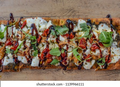Chicken and Mozzarella Flatbread Pizza with herbs, tomatos and pesto sauce on wooden plate. Top View.