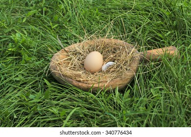 Chicken nest in old wooden bowl on a green grass