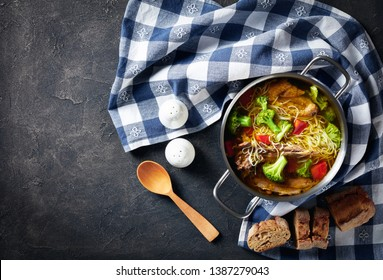 chicken noodle soup with broccoli, carrots and spices in a saucepan with spoon, kitchen towel and sliced baguette on a concrete table, flatlay, copy space