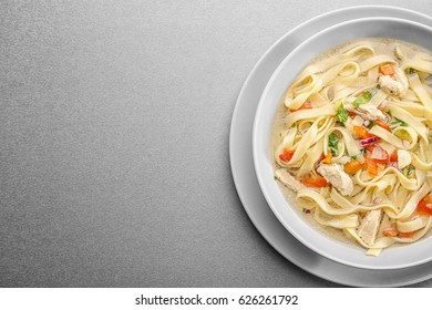 Chicken noodle soup in plate on grey background