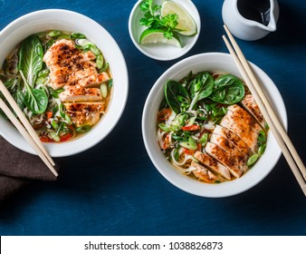Chicken, noodles and vegetables asian style soup on a blue background, top view