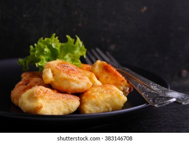 chicken nuggets in a black plate on a black background