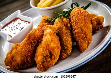 Chicken nuggets with french fries on wooden table