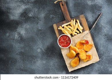Chicken nuggets and French fries on a wooden board. Next cup with ketchup. One of the nuggets is pinned on the fork. View from above. Gray background. Free space for text.