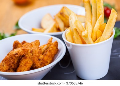 Chicken nuggets with french fries and potato wedges