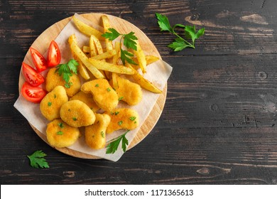 Chicken nuggets, french fries and sauces on dark wooden background, copy space. Fried nuggets and potato with ketchup and mayonnaise.