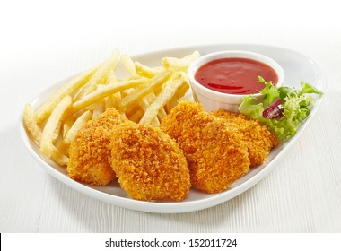 chicken nuggets and fried potatoes on a white plate